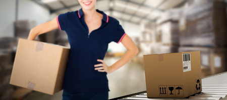clothing store: Happy delivery woman holding cardboard box  against many stack of cardboard boxes