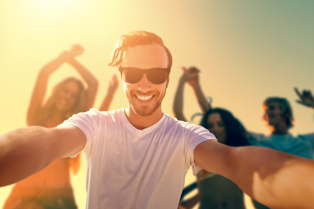 personas festejando: Smiling man taking a seflie against group of friends dancing at beach during sunset