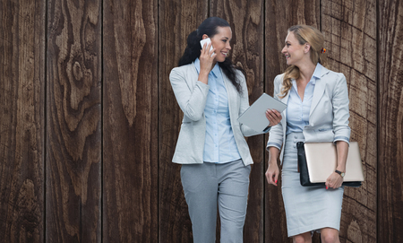 Businesswomen using mobile phone while walking  against wood panelling