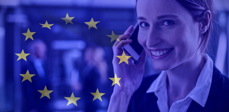 European flag against smiling businesswoman talking on mobile phone in office corridor