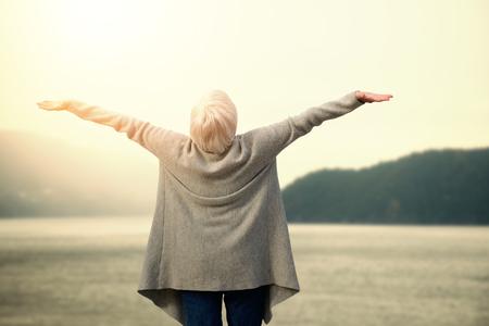 Ltere Frau , die gegen szenische Ansicht des Sees und des Berges ausdehnt Standard-Bild - 82504747