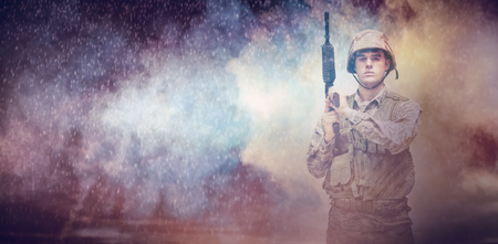 carrying: Cloudy sky landscape against military carrying a rifle on his shoulder