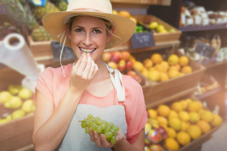 clothing store: Portrait of smiling young woman eating grapes against fruits arranged in super market