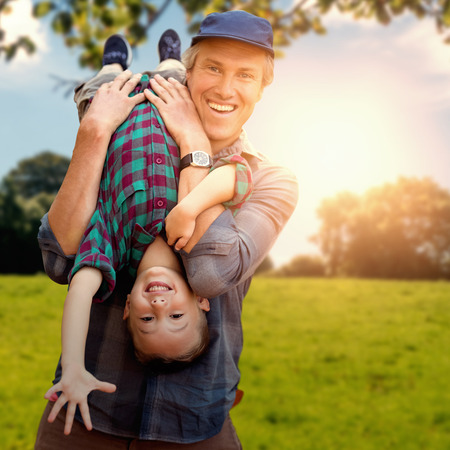 father holding his son upside down against green field against a green forest ans blue sky Stock Photo