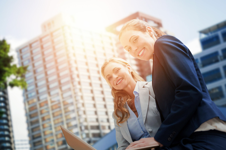 Portrait of business women posing with laptop against beautiful cityscape against clear sky Stock Photo