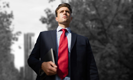 Low angle view of businessman holding digital tablet against towers seen through trees in city Stock Photo
