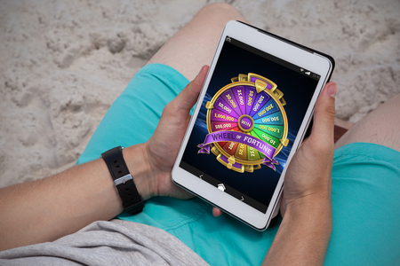 peace risk: Colorful wheel of fortune on mobile display against man using digital tablet on the beach Stock Photo
