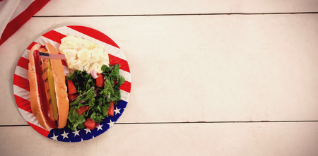 Overhead view of hot dog with American flag in plate on table Stock Photo
