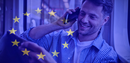 European flag against handsome man holding newspaper while talking on mobile phone