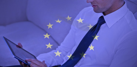 european culture: Attractive businessman using digital tablet against european flag Stock Photo