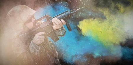 defocussed: black against military aiming his rifle Stock Photo