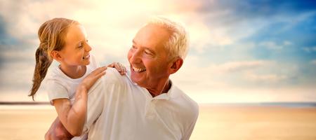 穏やかなビーチの風景に対して彼の背中に彼の孫を保持の祖父 写真素材