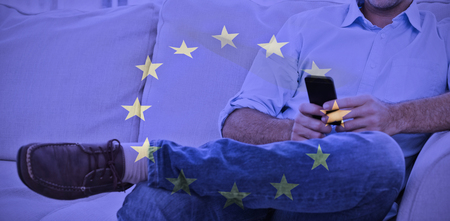Cheerful man sitting on the couch using his smartphone against european flag