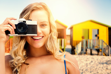fizz: Smiling girl taking a photo against multi colored huts on sand against clear sky Stock Photo