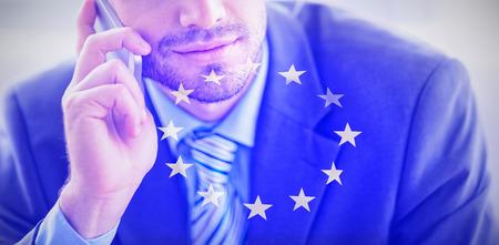 Handsome businessman sitting on sofa making a call against european flag