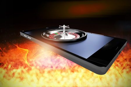 3D image of mobile phone with roulette wheel against defocused image of illuminated lighting equipment