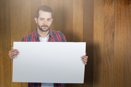 Portrait of young man holding blank placard against wooden surface with planks