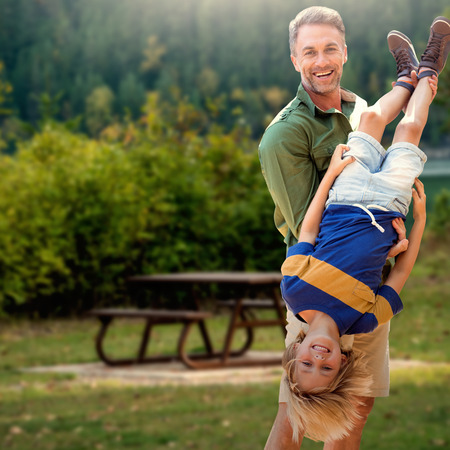 Father holding son upside-down  against bench beside lake in forest park