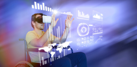 Man using virtual reality glasses while sitting on wheelchair against blur view of modern meeting room Stock Photo