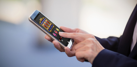 Slot machine app on mobile display against businesswoman using mobile phone Reklamní fotografie - 82553554