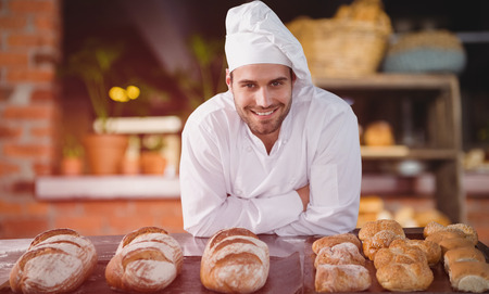 Portrait of male chef standing by bread at table against empty counter at coffee shop