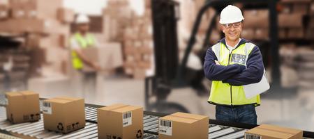 Worker wearing hard hat in warehouse against warehouse worker loading up pallet