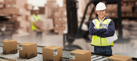 Worker wearing hard hat in warehouse against warehouse worker loading up pallet