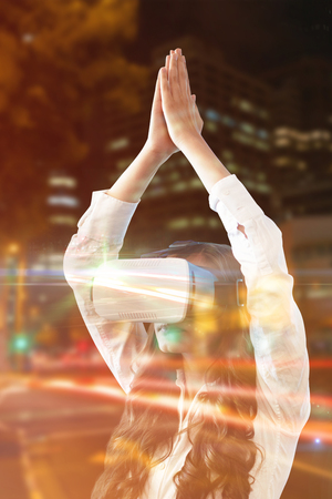 virtual reality simulator: Young woman practicing yoga while wearing virtual reality glasses against illuminated roads by building in city