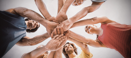 Directly below shot of friends standing with stacked hands against sky Stock Photo
