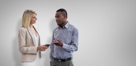 Smiling businesswoman and businessman are conversing against grey vignette