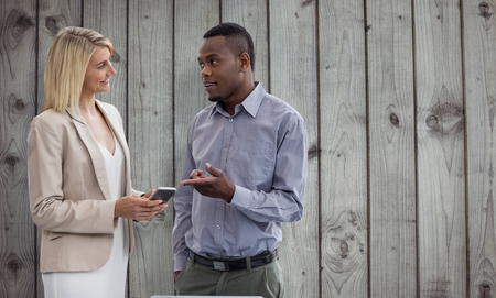 two persons only: Smiling businesswoman and businessman are conversing  against close-up of wooden fence Stock Photo