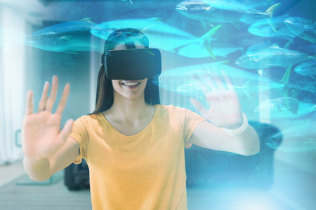 Happy young woman gesturing while using virtual reality glasses against fish swimming in a tank