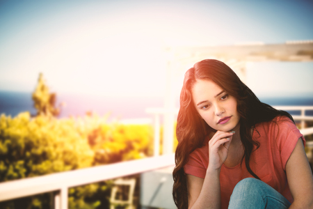 Thoughtful Young Woman Relaxing On Tiled Floor against scenic view of sea against sky