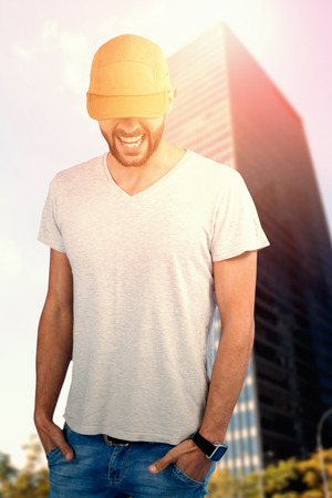 Portrait of handsome man wearing hat against skyscraper