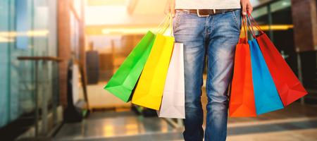 Samengesteld beeld van lage sectie van de mens die kleurrijke het winkelen zak draagt