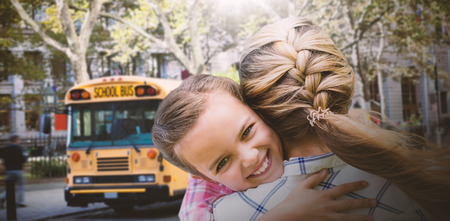africa kiss: Mother and daughter hugging  against schoolbus on ny street