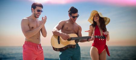 plucking: Friends playing music in swimwear against idyllic view of sea Stock Photo