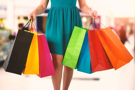 Women holding shopping bag  against interior of modern shopping mall