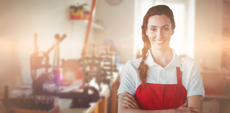 Portrait of confident female owner with arms crossed against workshop with machinery