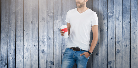 Handsome man posing with cup of coffee  against wooden planks background