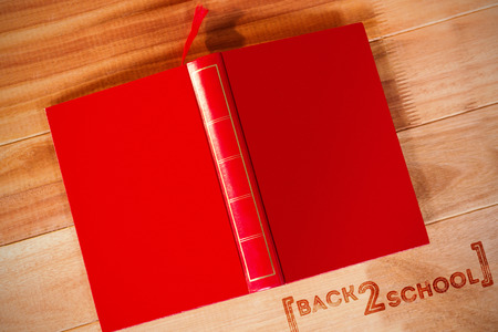 Back to school text over white background against open book upside down on table