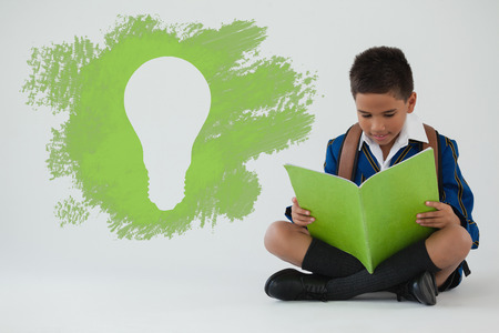 Digital composite image of light bulb on black spray paint against schoolboy reading book on white background Stock Photo