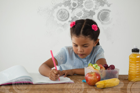 Digital composite image of gears on black spray paint against schoolgirl doing her homework against white background