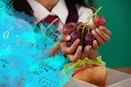 Digital composite image of algebraic formulas against schoolgirl having grape fruit