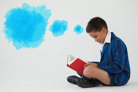Digital composite image of blue spray paint against schoolboy reading book on white background