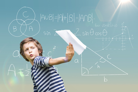 Playful boy holding paper airplane against blue sky Stock Photo