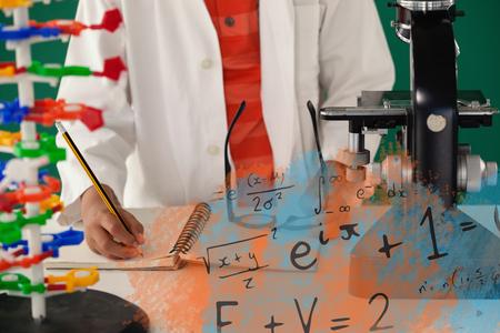 Illustration?áof algebraic formulas against schoolboy writing on book against green background Stock Photo