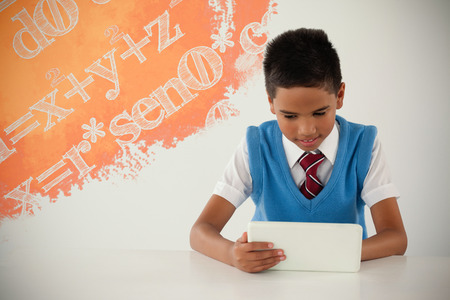 Graphic image of equations against schoolboy using digital tablet