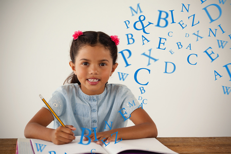 letters against young girl writing in her book against white background Stock Photo