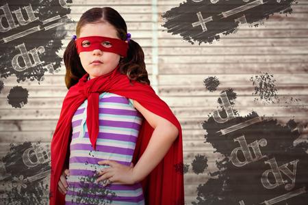 Portrait of girl standing in superhero costume against digitally generated grey wooden planks